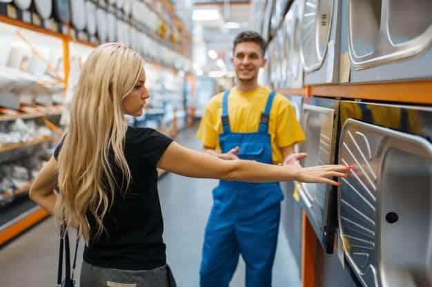 พนักงานขายโน้มน้าวลูกค้าในซื้อซิงค์ล้างจานในร้านวัสดุก่อสร้าง